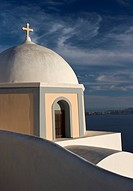 Greece, Santorini. Church dome against clouds and blue sky with Aegean Sea in background. Credit: Bill Young / Jaynes Gallery / DanitaDelimont.com