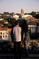 Portugal, Barcelos. Young couple on hill above city with cathedral in the distance.