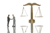Miniature businessmen figures shaking hands in front of a balanced scale, symbolic image for balanced business