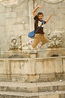 Croatia, Dalmatia, Dubrovnik. Boy jumping from the Big Fountain of Onofrio 15th century. The historic center of Dubrovnik is a UNESCO World Heritage s...