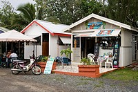 French Polynesia, Cook Islands, Rarotonga, Avarua. Customers sit outside teahouse and another business in the cultural market. Credit: Wendy Kaveney /...