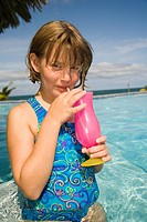 Girl age 7 drinks soda at poolside bar, Jaguar Reef Lodge, Hopkins, Stann Creek District, Belize. MR/PR