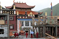 Tibetan monks in red robes standing and walking in the rain through the construction site at the Lhagang monastery, Lhagang Gompa, Kham, Tibet, Tagong...