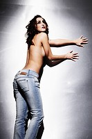 Woman with bare torso and in and jeans leaning lasciviously on a metal wall