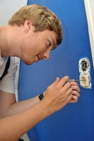 Young man screwing socket into wall