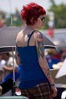 USA, Louisiana, New Orleans. Female Jazz and Heritage Festival attendee with red hair and tattoos. Credit: Wendy Kaveney / Jaynes Gallery / DanitaDeli...