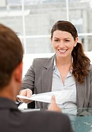Happy businesswoman giving a paper to a male colleague during a meeting in the office