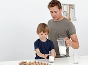 Handsome man giving milk to his son standing in the kitchen
