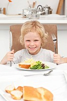 Portrait of a little boy ready to eat pasta and salad in the kitchen