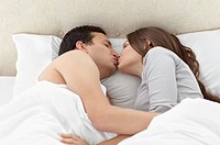 Lovely couple kissing in each others arms on the bed at home