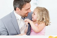 Little girl adjusting the tie of her father