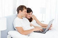 Young couple watching videos on their computer at home