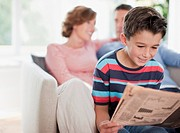 Boy reading newspaper with parents in background