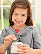 Smiling girl putting money into coin purse