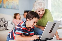 Grandmother watching grandson use laptop