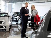 Salesman talking to woman in automobile showroom (thumbnail)
