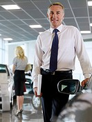 Salesman standing in automobile showroom (thumbnail)