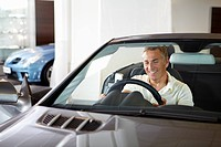 Smiling man sitting in new car in showroom