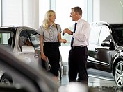 Salesman handing woman car key in automobile showroom
