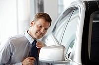 Salesman adjusting tie in side mirror of new car in showroom