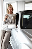 Woman with key leaning on new car in showroom