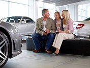 Family looking at brochure in automobile showroom
