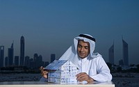 Young Arab man sitting at a desk with Dubai City in the background holding a house made of money