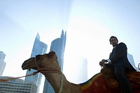 Businessman sitting on camel, towers seen through the mist in the background
