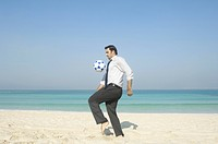 Businessman playing with football