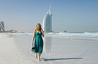 Young lady on the beach in front of the famous landmark of Dubai