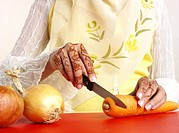 Woman cutting carrot,midsection
