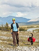 Young woman hiking, pack dog, Alaskan Husky, sled dog, carrying a dog pack, backpack, Wind River and Mackenzie Mountains behind, Yukon Territory, Cana...