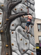Child climbing a practice wall at a street fair  Toronto, Ontario, Canada