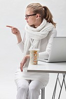 Blonde young woman dressed in white next to a laptop