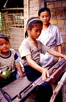 Mother teaching her daughter to weave sitting at a loom in a village in Laos, Asia