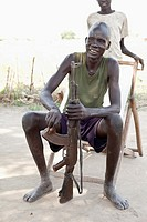 Dinka man cleaning ak-47 in Lilir Sudan, December 2010