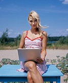 Young woman using latop while sitting on the blue table on the beach