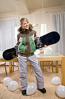 Young woman with snowboarding equipment.