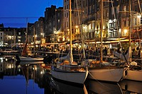 Sailing boats and tourists at pavement cafés / sidewalk cafes along the quay of the Honfleur harbour at night, Normandy, France