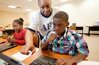 Detroit, Michigan - A teacher helps children working on computers during the Summer Literacy Camp organized by the American Federation of Teachers for...