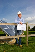 Technician holding blueprints standing near large solar panels