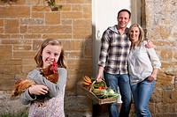 Girl holding a chicken, parents holding basket of vegetables