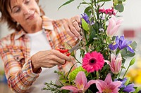 Smiling woman trimming flowers in floral arrangement in classroom