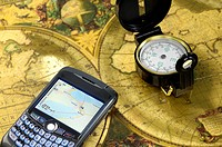 Modern Blackberry device with Global Positioning System, GPS, and a compass on a world map