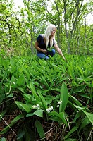 Blond woman picking flowers, Lily of the Valley Convallaria majalis