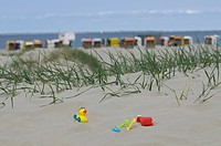 Holidays, children´s toys on a sand dune in front of roofed wicker beach chairs on a beach and the sea, Norddeich, Norden, East Frisia, Lower Saxony, ...