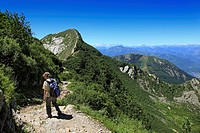 Woman hiking in the mountains to Monte Tamaro, Ticino, Switzerland