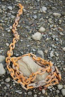 Mooring chain wrapped around a rock on the seacoast