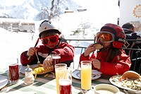 Skiing children at lunch break on hotel terrace, Hirschegg, Kleinwalsertal, Vorarlberg, Austria