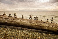 Rock figures on log by ocean, Vancouver Island, British Columbia, Canada